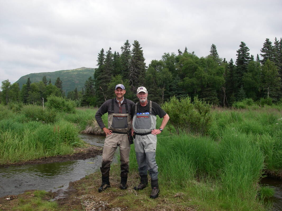 Aaron Wirsing and friend standing near stream in natural area